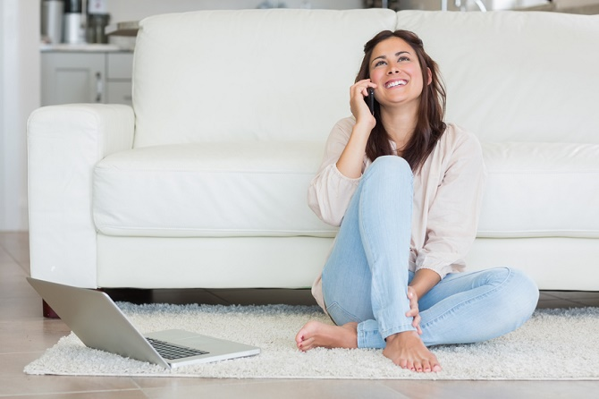 Smiling woman on the phone in front of laptop in living room