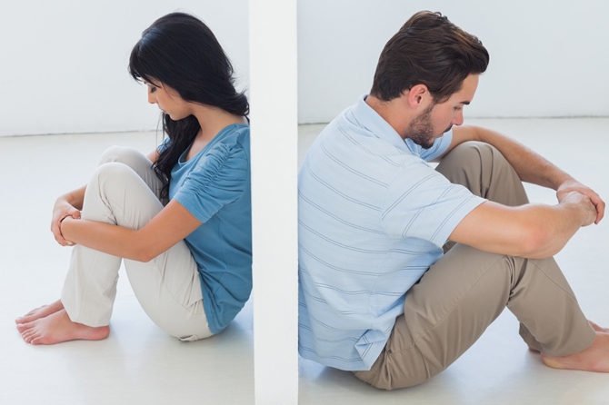 Sitting couple are separated by white wall and looking depressed