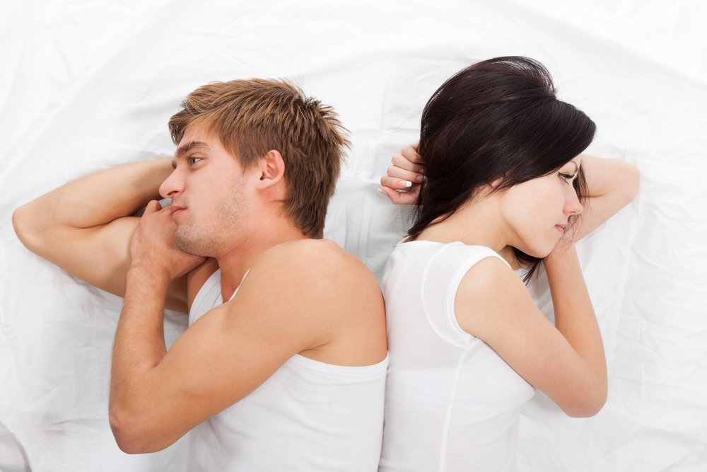 young upset couple lying separate in a bed