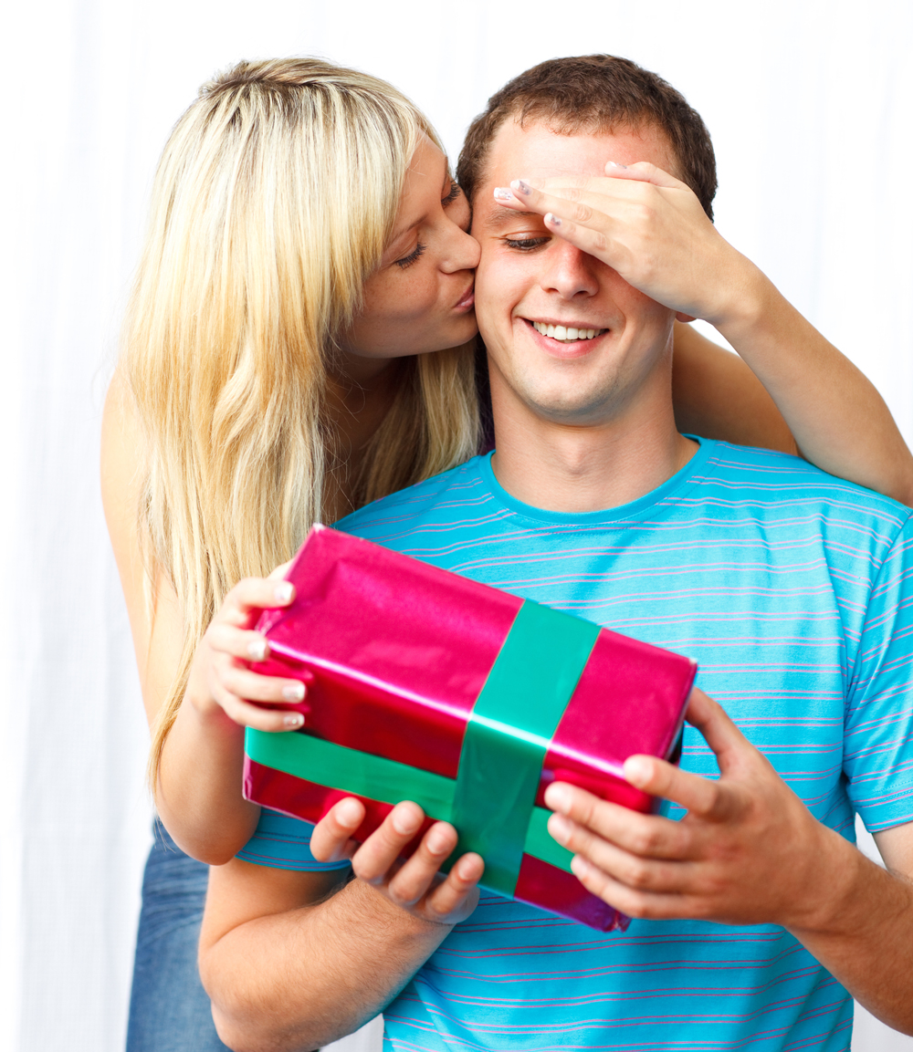 Woman giving a present and a kiss to a man