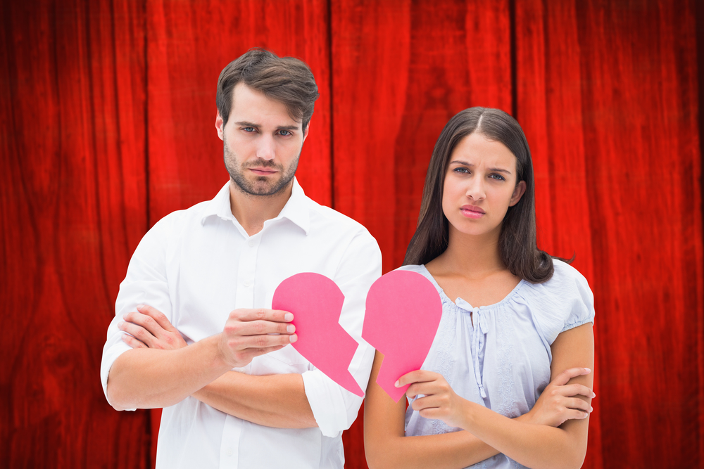 Upset couple holding two halves of broken heart against red wooden planks