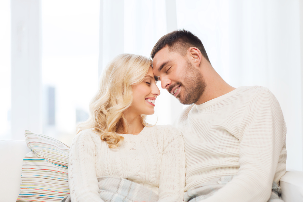 happy couple covered with plaid on sofa at home