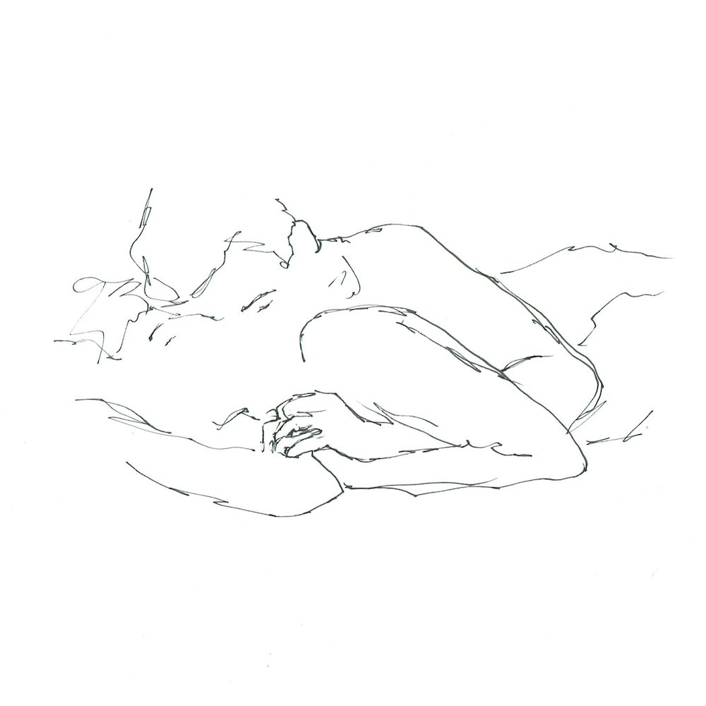 man lying on top of a woman kissing her neck, arm under her arm and holding her hand lovingly