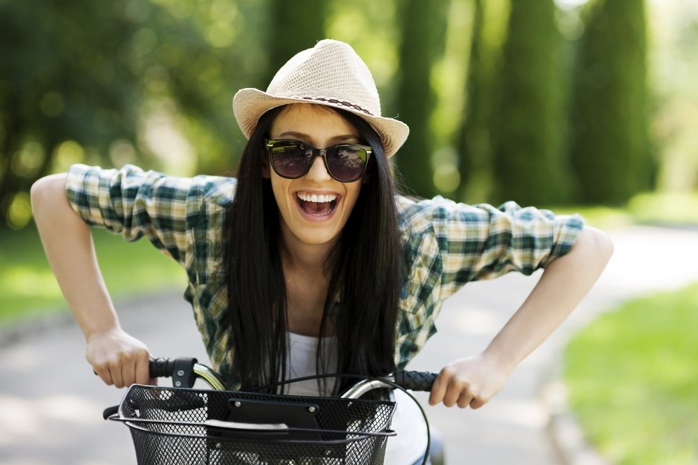 woman in hat and sunglasses on bicycle looking at camera