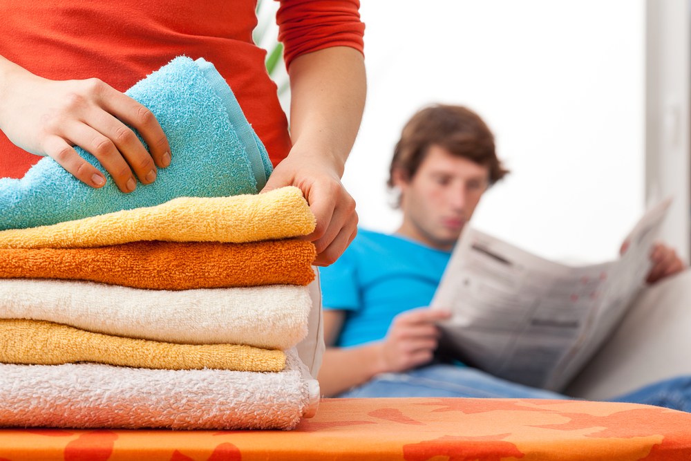 man sitting on couch out of focus and woman thumbing through stacks of clothes wondering is he using me