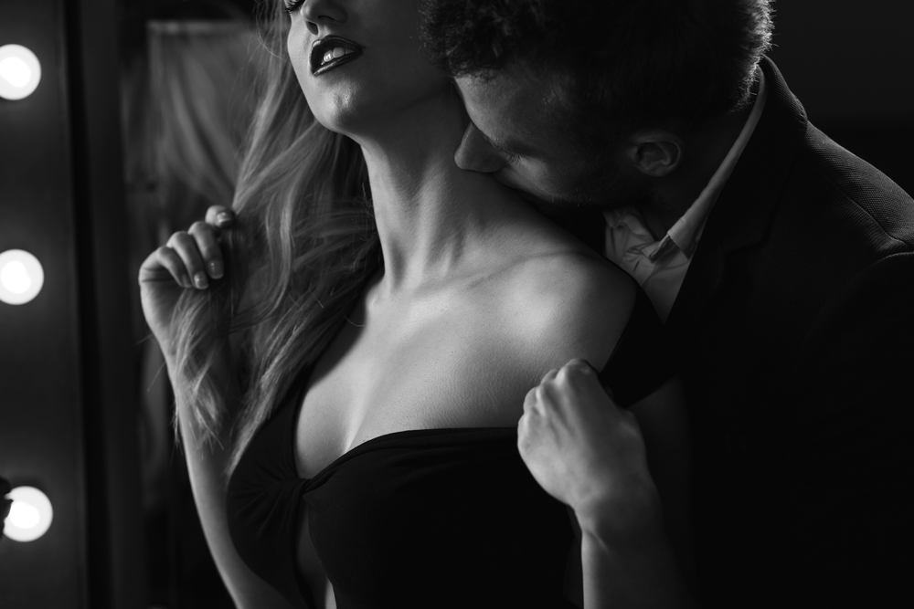 man kissing woman on the neck from behind, one of her erogenous zones